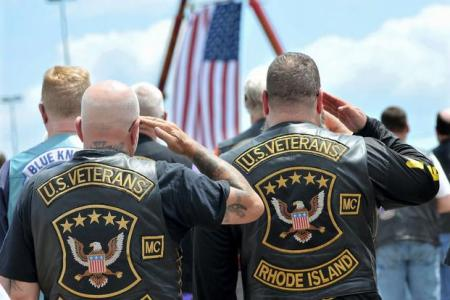 Members of the U.S. Veterans Motorcycle Club salute the flag during the playing of the National Anthem at the beginning of a memorial and remembrance service for seven motorcyclists and their spouses who died in the June crash Saturday, July 13, 2019 in the parking lot of Gillette Stadium in Foxboro, Mass. The seven bikers were killed when a pickup truck hauling a flatbed trailer slammed into a group of riders in Randolph, New Hampshire. (Mark Stockwell/The Sun Chronicle via AP)