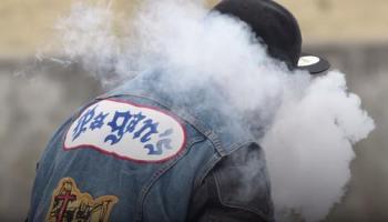 Pagan's MC biker smoking with back turned, wearing a black baseball cap.