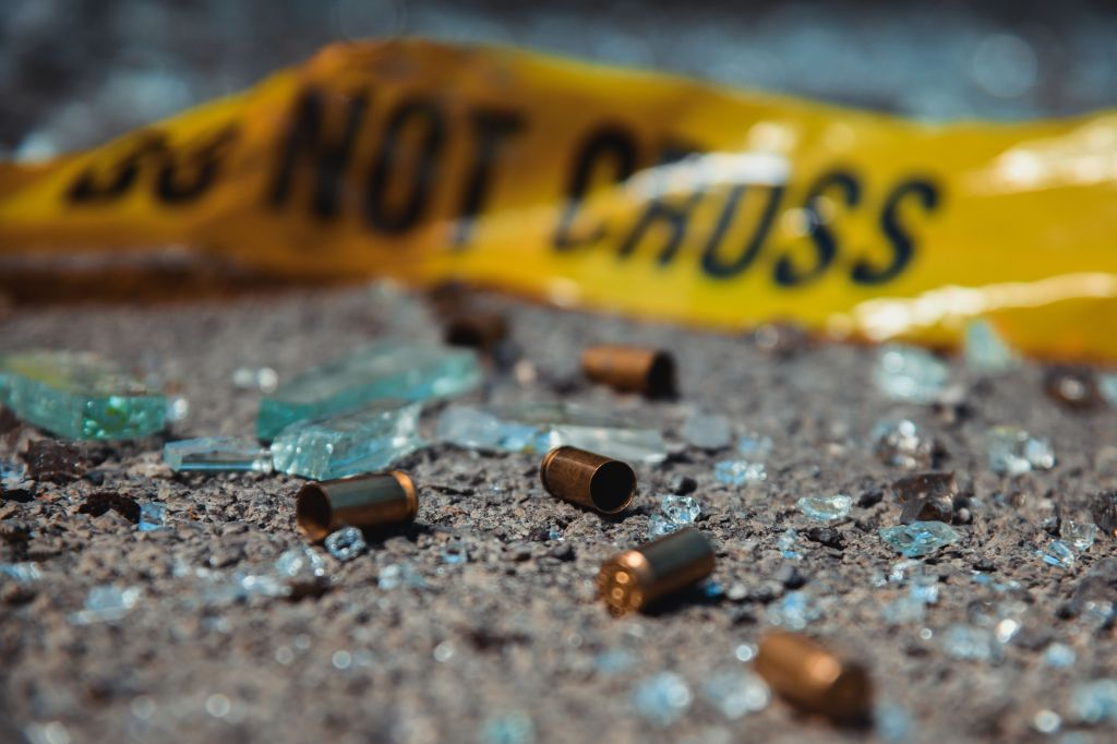 Police yellow tape with bullet casings lying on the ground mixed with broken glass.